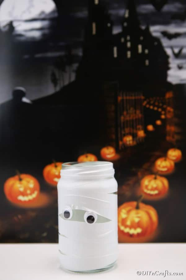 A mummy mason jar light sitting on a white table with a dark background of pumpkins lining a walkway in the background