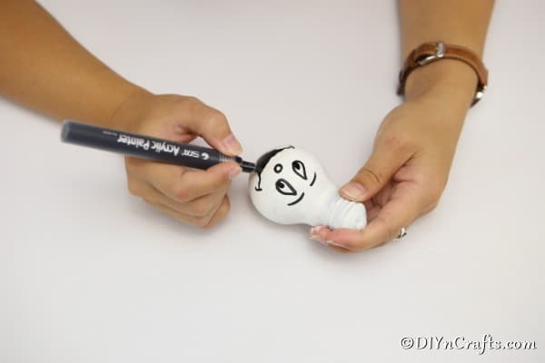 Painting a face on the ghost decorative light bulbs