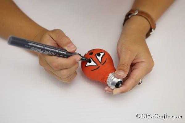 Painting a face on the pumpkin decorative light bulbs