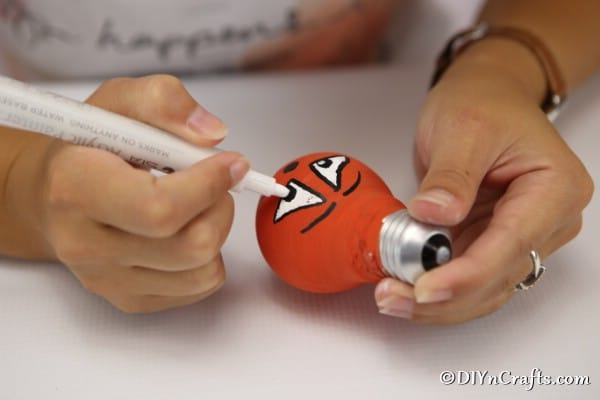 Drawing face on orange painted decorative light bulb