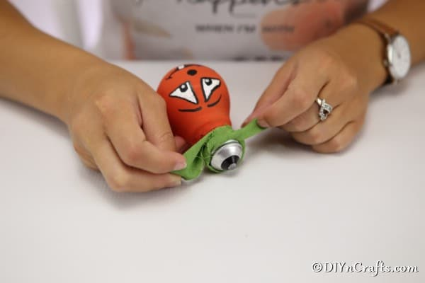 Tying a green ribbon on the top of a pumpkin decorative light bulb for halloween