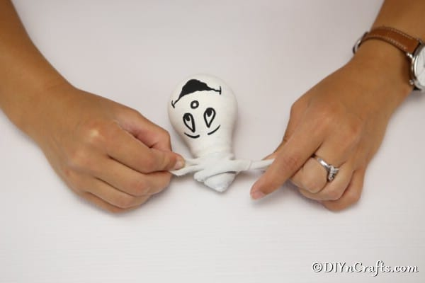Tying a ribbon on the ghost decorative light bulbs