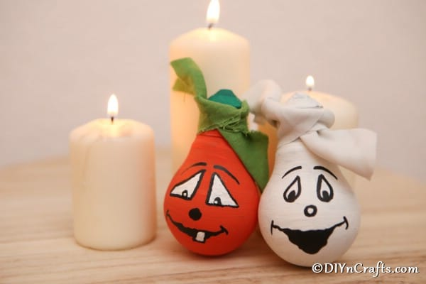 Decorative halloween light bulbs leaned against candles sitting on a wooden table