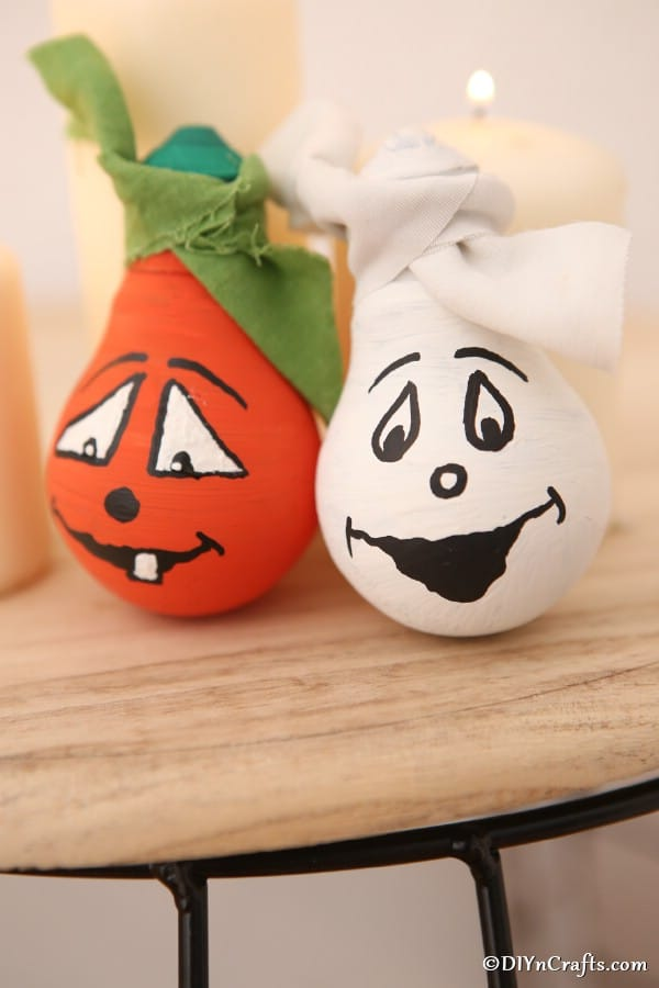 Two decorative light bulbs decorated for halloween sitting on wooden stool