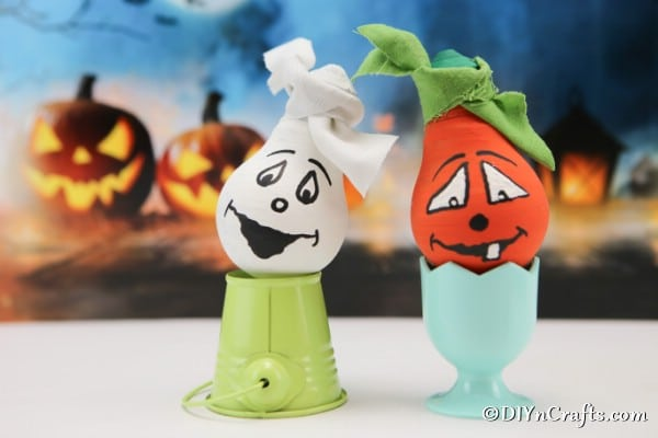 Completed halloween decorative light bulbs painted and sitting on egg cups to display with pumpkins in background