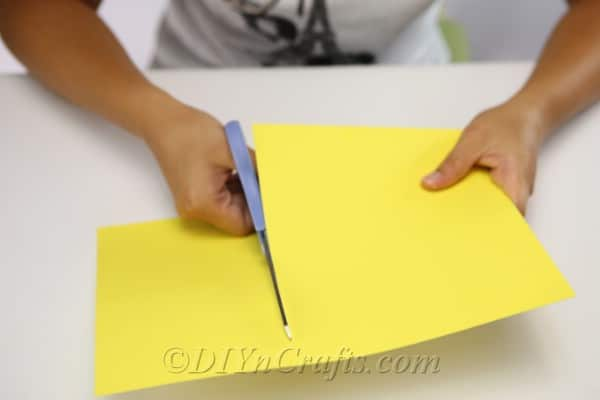 Cutting yellow paper to create core of scarecrow craft body