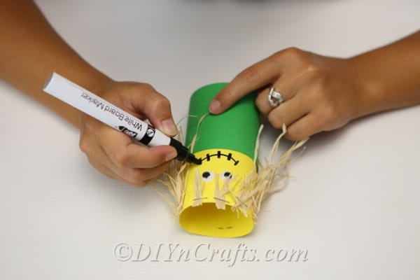 Drawing a face on the paper scarecrow craft with a permanent marker