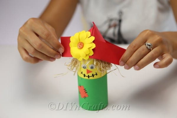 A woman placing the hat on top of the scarecrow paper craft