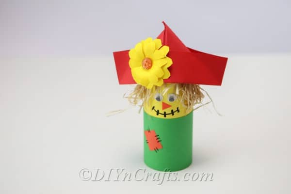 Completed scarecrow craft sitting on a white table