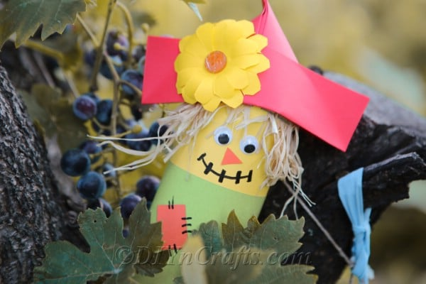 Paper scarecrow craft sittinge outside in a grape vin