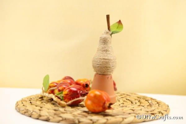 A twine wrapped pear fruit decoration sitting on a woven mat
