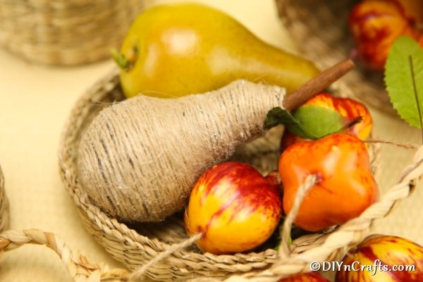 A basket full of fruit pieces including the wrapped pear fruit decoration