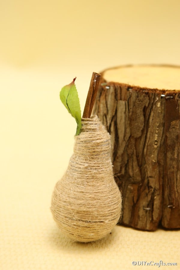 A single twine wrapped fruit decoration sitting leaned up against a piece of a wooden log