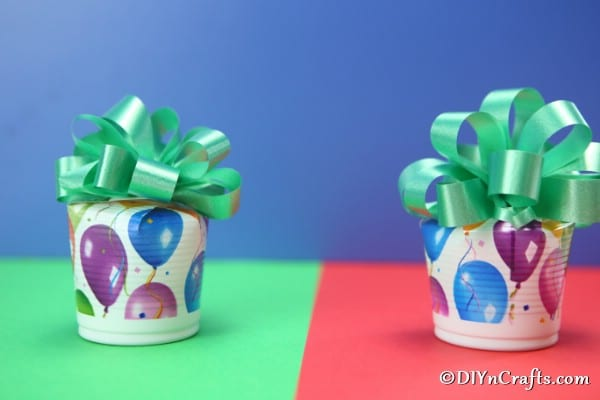 An up close picture of completed party cup cookie boxes sitting on a green and red surface