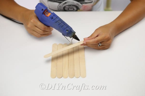 Gluing craft sticks together to create a scarecrow head