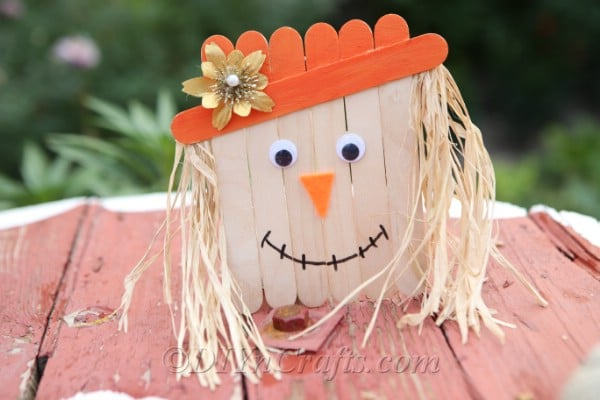 A completed scarecrow craft sitting on a wooden table outside