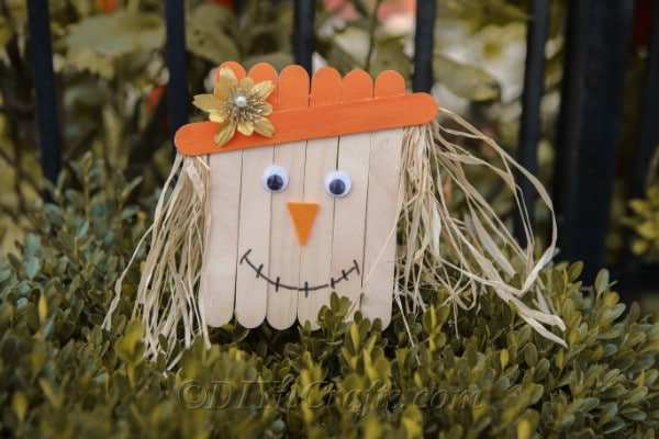 A finished scarecrow head sitting on a shrub outside against a black fence