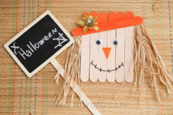 How to make a scarecrow out of craft sticks sitting on a cloth with a halloween sign