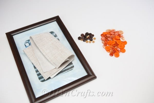 Supplies for pumpkin button art laying on a white table