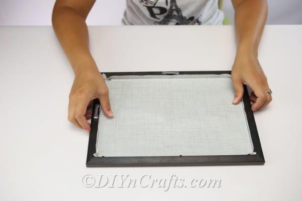Measuring fabric against frame for pumpkin button art