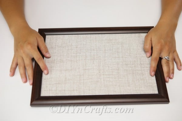 Attaching fabric to picture frame to create pumpkin button art
