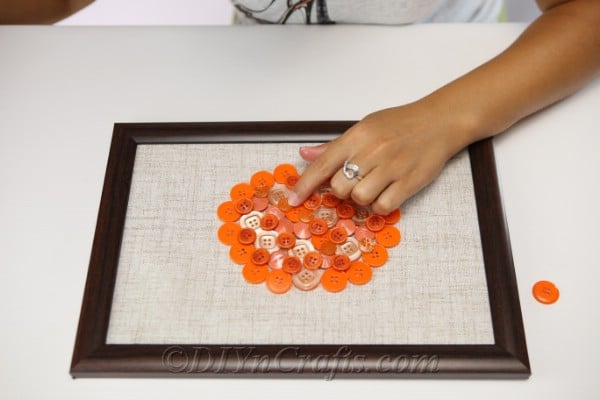 Gluing buttons onto fabric to create pumpkin button art