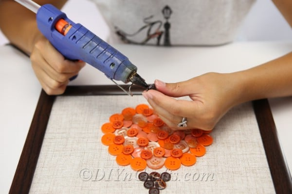 Adding the brown buttons to create the stem of the pumpkin button art piece