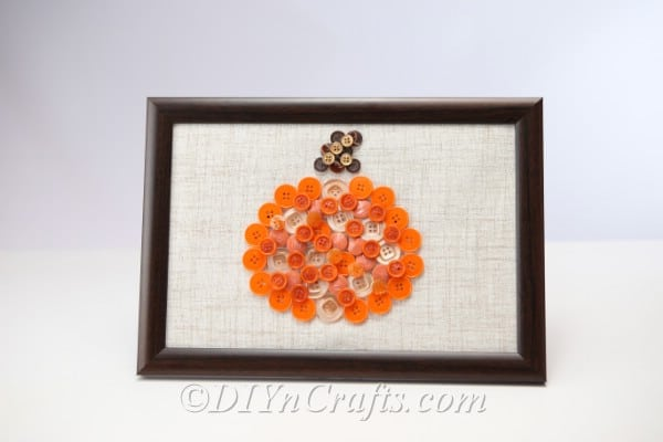 Farmed pumpkin button art on a white wall