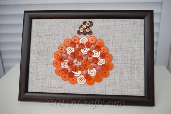 Finished pumpkin button art fall decor sitting on a white counter
