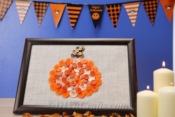 Finished pumpkin button art sitting in front of a black and white bunting with blue surface in background