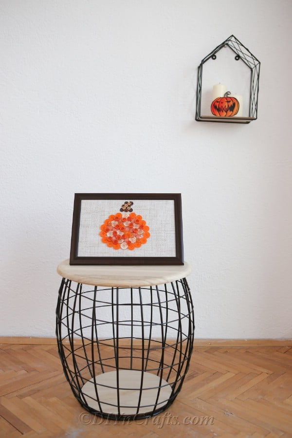 Pumpkin button art craft displayed on a wooden and wire stool piece against a white wall