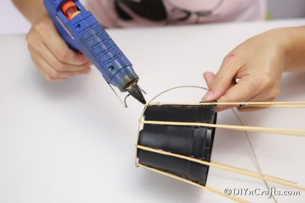 Gluing dowels to the flower pot for making a woven basket