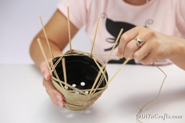 Weaving thread in and out of dowels to create woven basket