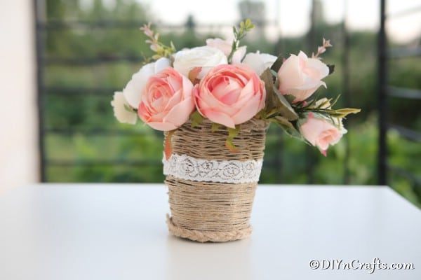 Rustic woven basket sitting on a white counter with shrubs in the background