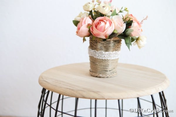 The completed rustic woven basket sitting on a wooden stool