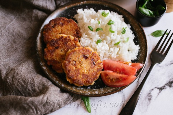 A plate of salmon patties with rice and tomato on the side