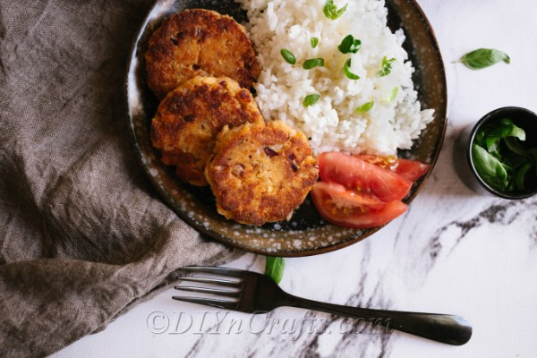 An overhead plate of salmon patties on a dark plate with rice on the side