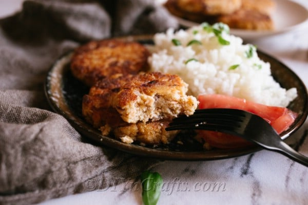 An up close image of a plate of an easy salmon patty recipe with rice and vegetables