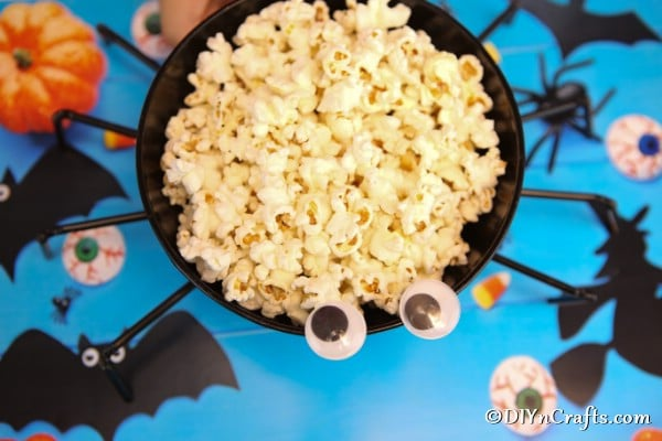 Overhead picture of halloween spider bowl on a blue surface and filled with popcorn