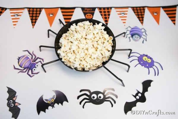 An overhead picture of the halloween spider bowl filled with popcorn and sitting on a purple halloween paper
