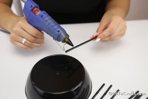 Gluing straws to bottom of halloween spider bowl