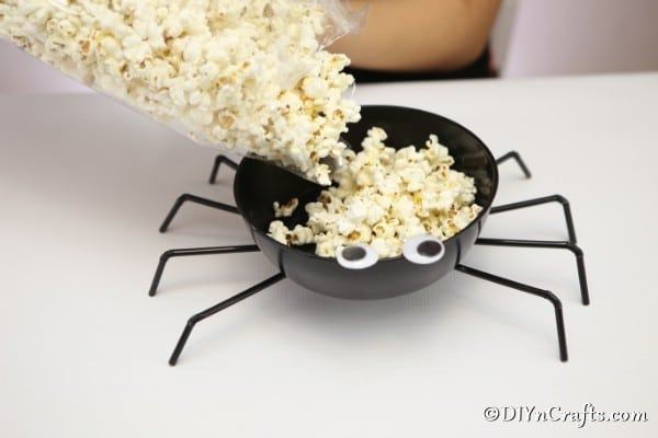 Filling the halloween spider bowl with popcorn