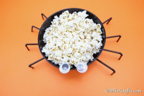 Overhead picture of halloween spider bowl sitting on orange surface