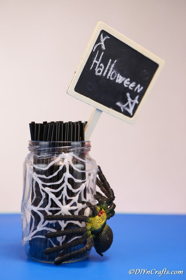 A halloween spider web jar sitting on a blue surface with a halloween sign and knives inside the jar