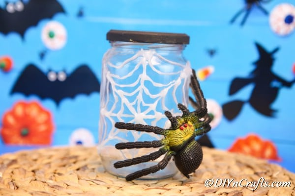 A halloween spider web jar on a brown surface with blue halloween themed background