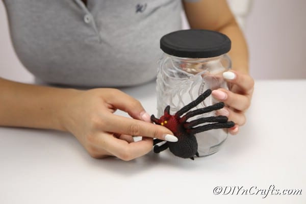 Attaching the plastic spider to the halloween craft jar