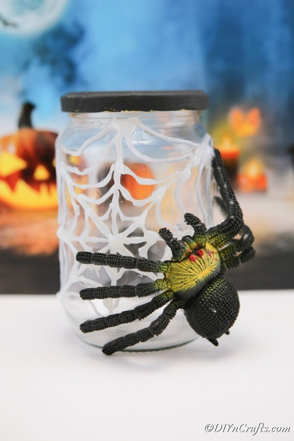 Completed halloween spider jar sitting on white surface with blue halloween themed background