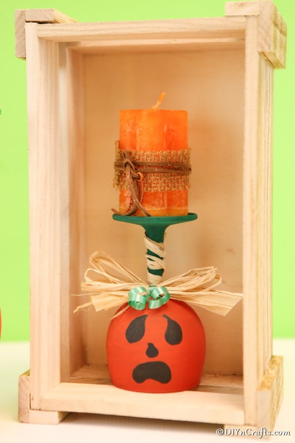 A single pumpkin wine glass sitting inside a wooden box display
