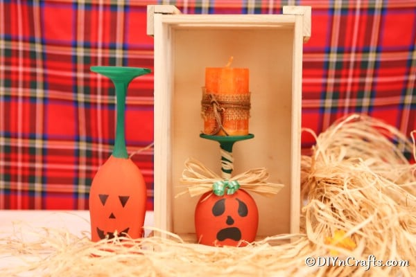 Two wine glass pumpkins displayed in and by a wooden box with a red plaid background