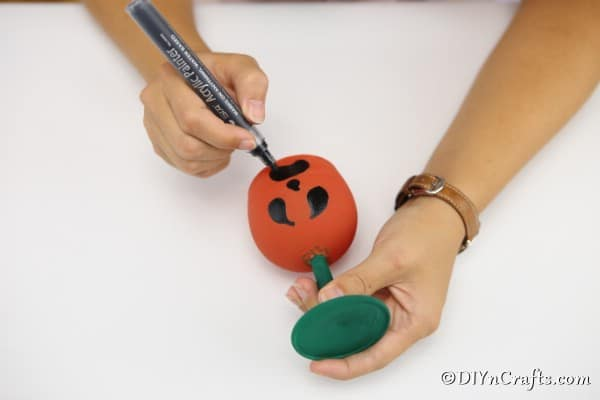 Drawing a face on the dry painted wine glass pumpkin
